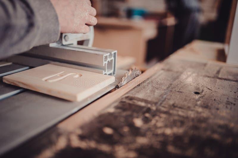 En snickare arbetar på snickeri maskinhjälpmedlet Sågmöblemangdetaljer med en cirkelsåg arkivfoto