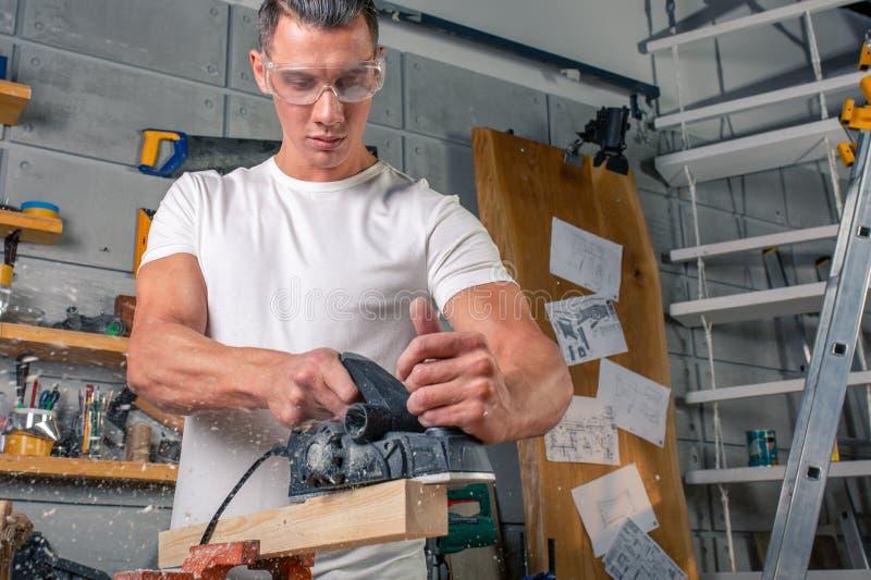 En snickare arbetar på snickeri maskinhjälpmedlet Sågmöblemangdetaljer med en cirkelsåg Process av att såga delar royaltyfri bild