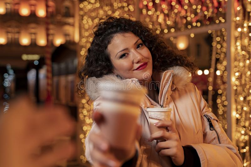 En snygg hårflicka i staden som har dekorerats med julljus royaltyfri foto