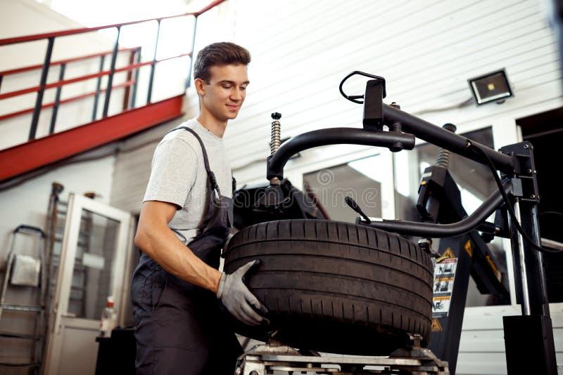 En snygg mekaniker reparerar ett hjul på en bilservice arkivfoton