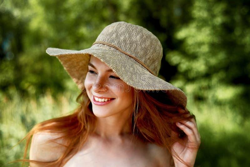 En sofistikerad rödhårig flicka i en enkel linneklänning, i en ljus bredbrättad hatt se modellen naturlig skönhet royaltyfri bild