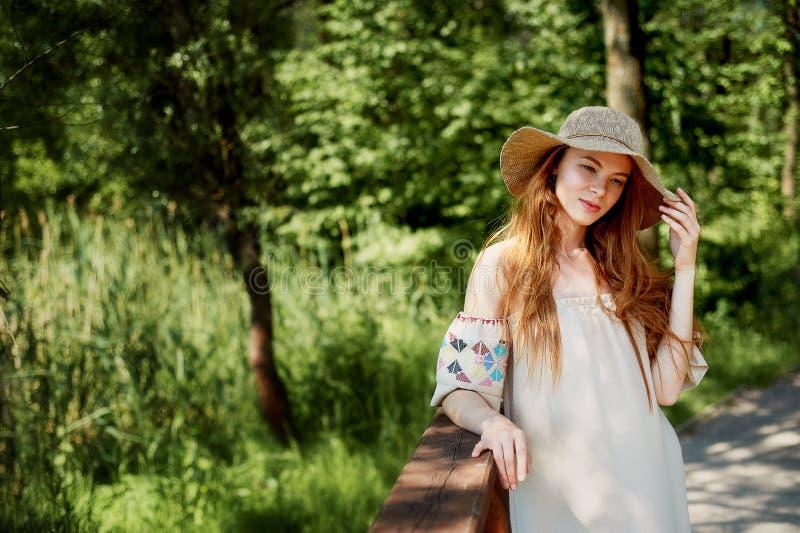 En sofistikerad rödhårig flicka i en enkel linneklänning, i en ljus bredbrättad hatt se modellen naturlig skönhet royaltyfri foto