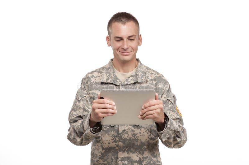 Militär man som ser en datortablet royaltyfri foto