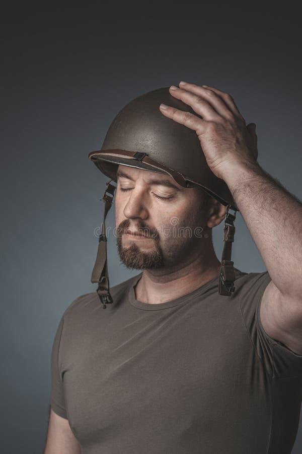 En soldats porträtt med handen på hjälmen och hans ögon stängda arkivfoton