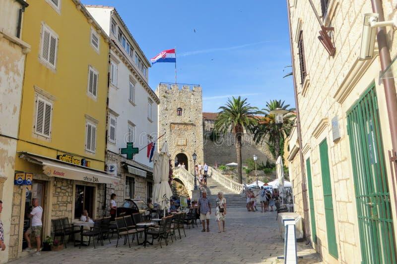 En solig sommardag på en gata med turister som går runt om att leda till ingången till Korcula den gamla staden royaltyfri foto
