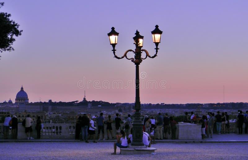 En solnedgång på Borghese Ville i Rome som beskådas av folk royaltyfri foto