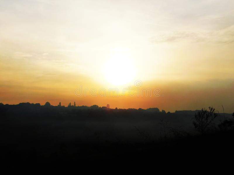 En solnedgång som fotograferas i himlen, som den ger ett guld- glöd till himlen fotografering för bildbyråer