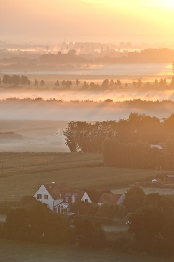 En soluppgång ovanför dimman royaltyfria foton