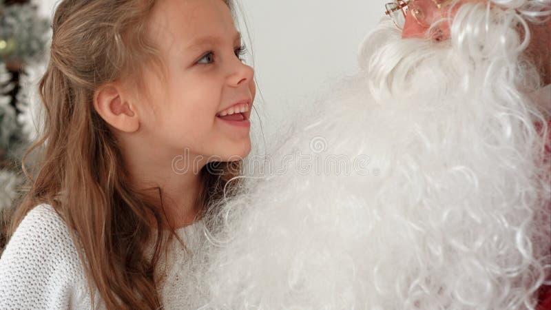 En souriant et lancez la fille partageant ses rêves de Noël avec Santa image libre de droits