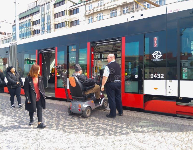 En spårvagnchaufför hjälper en person med handikapp skriver in en spårvagn i en elektrisk rullstol arkivbilder