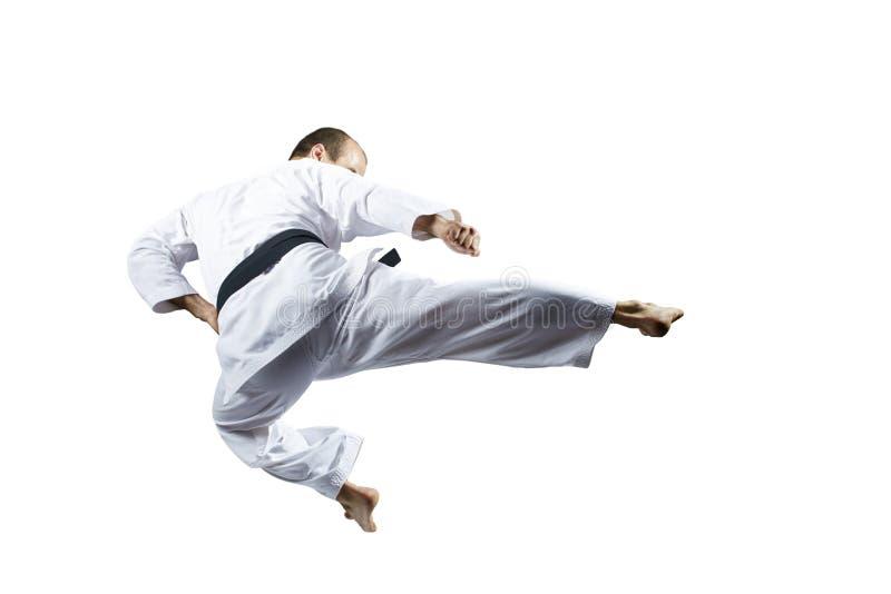 En spark som sparkas i hoppidrottsman nen, slår mot en isolerad vit bakgrund arkivfoto