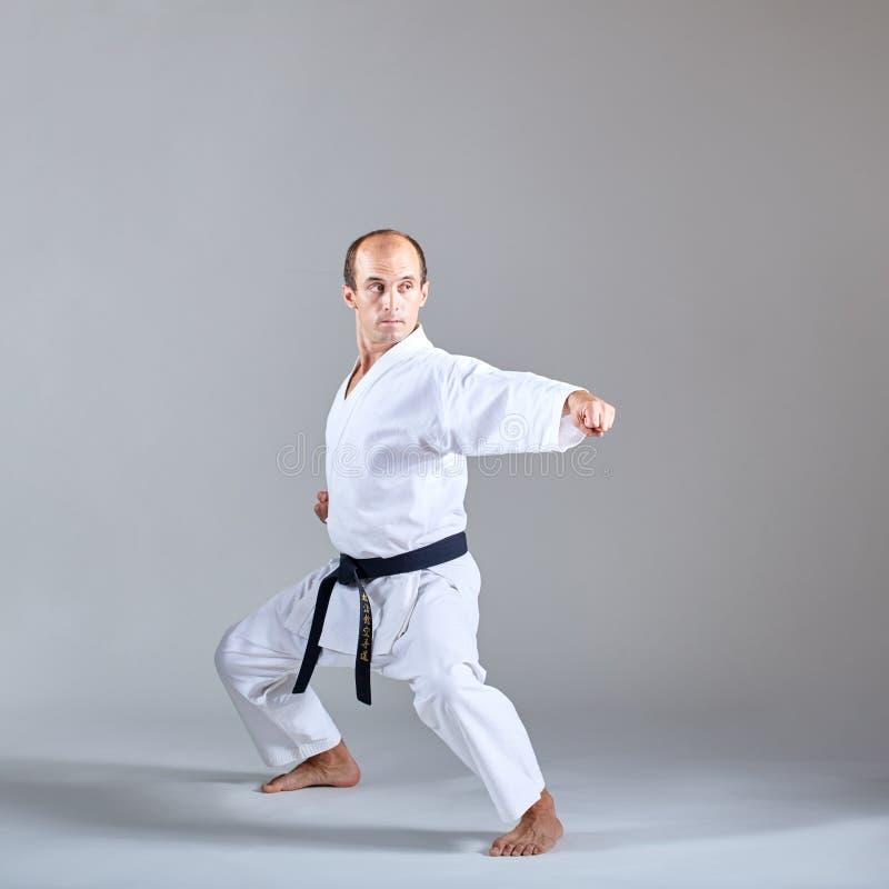 En spark utbildas av en idrottsman nen i en formell karateövning arkivbilder