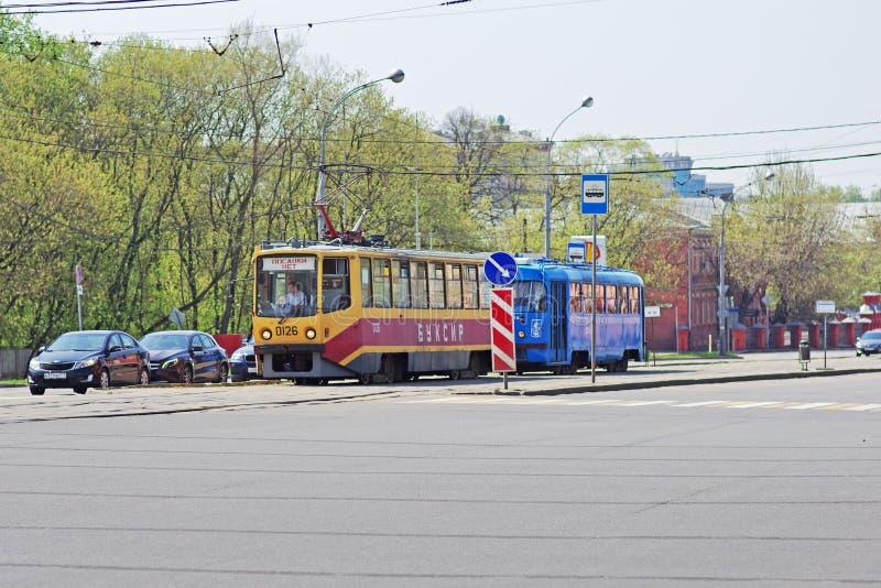 En special spårvagn-bogserbåt bogserar en defekt spårvagn längs en stadsgata i Moskva arkivbilder