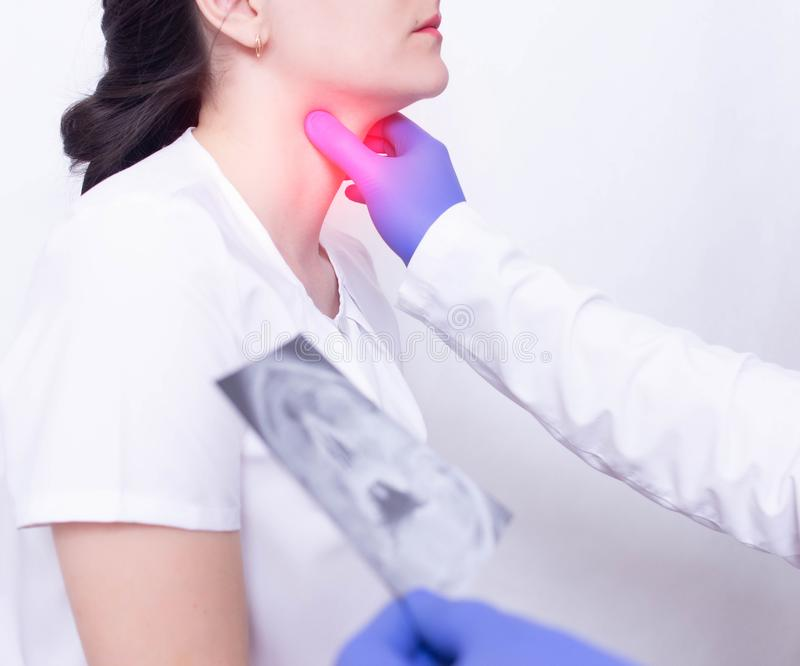 En specialistdoktor diagnostiserar en ?m hals f?r flicka s, genom att palpera f?r n?rvaron av inflammation och bulnad, ?m hals oc royaltyfri bild