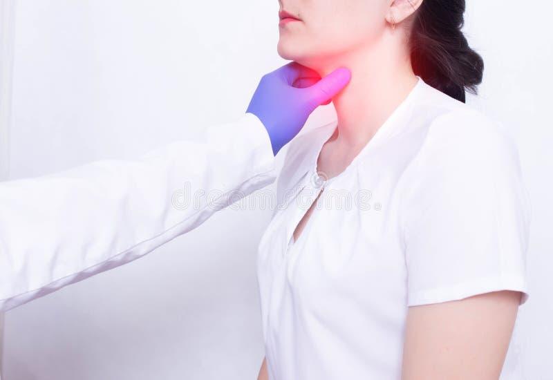 En specialistdoktor diagnostiserar och undersöker en flickas öm hals, närvaro av inflammation och bulnad, faryngiet och skav arkivbild