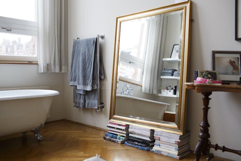En spegel på buntar av böcker i ett badrum royaltyfria bilder