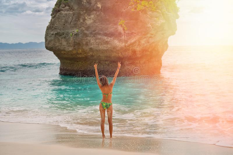 En spenslig brunbränd kvinna tycker om liv I bakgrunden vaggar inställningssolen och i havet kopiera avst?nd royaltyfri foto