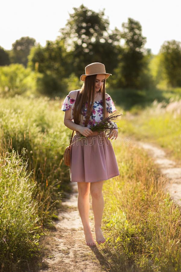 En spenslig flicka i en sugrörhatt och med en sugrörhandväska som rymmer en bukett av tusenskönor i ängen Sommarsolnedgång, begre royaltyfria bilder