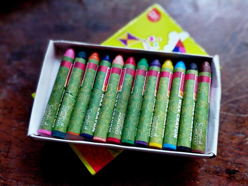 En splitterny ask för vaxfärgpenna med alla färger på plats royaltyfri foto