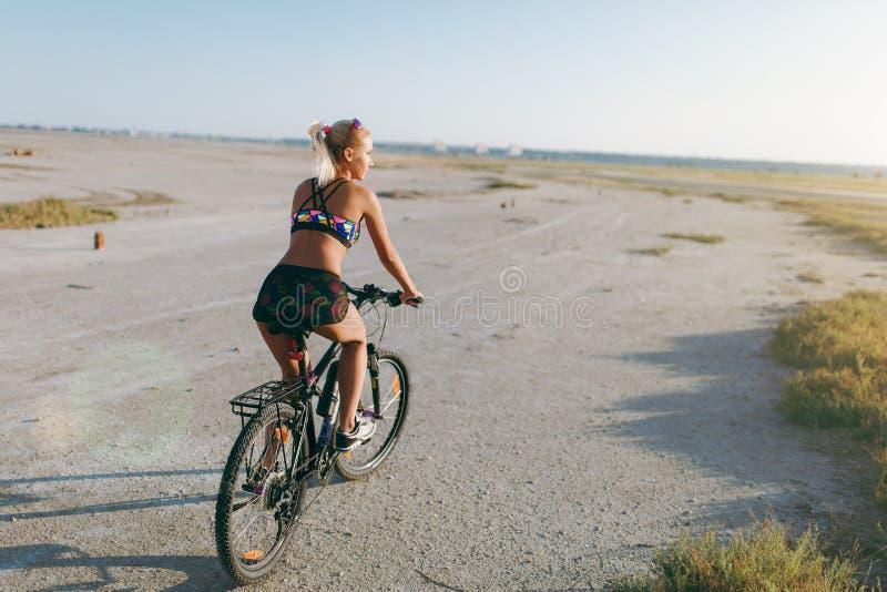 En sportig blond kvinna i en färgrik dräkt rider en cykel i ett ökenområde på en solig sommardag avkoppling för pilates för bollb arkivbild