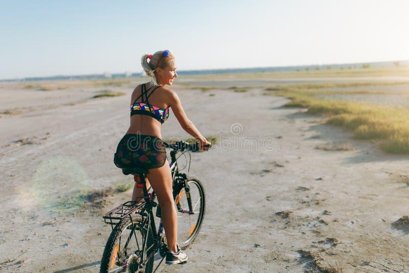 En sportig blond kvinna i en färgrik dräkt rider en cykel i ett ökenområde på en solig sommardag avkoppling för pilates för bollb royaltyfri fotografi