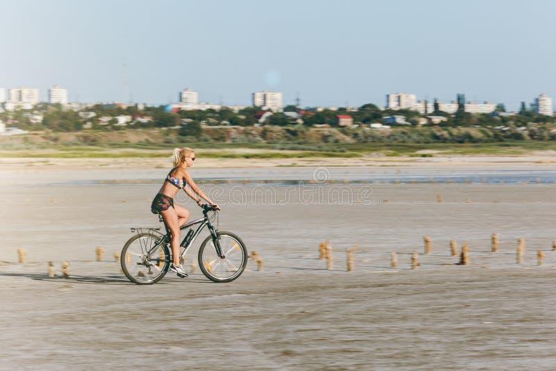 En sportig blond kvinna i en färgrik dräkt rider en cykel i ett ökenområde på en solig sommardag avkoppling för pilates för bollb arkivbilder