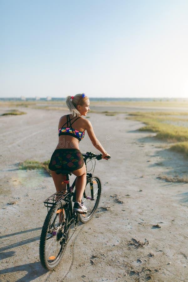 En sportig blond kvinna i en färgrik dräkt rider en cykel i ett ökenområde på en solig sommardag avkoppling för pilates för bollb royaltyfri foto