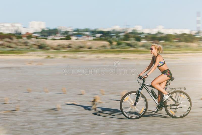 En sportig blond kvinna i en färgrik dräkt rider en cykel på snabb hastighet i ett ökenområde på en solig sommardag avkoppling fö arkivfoton