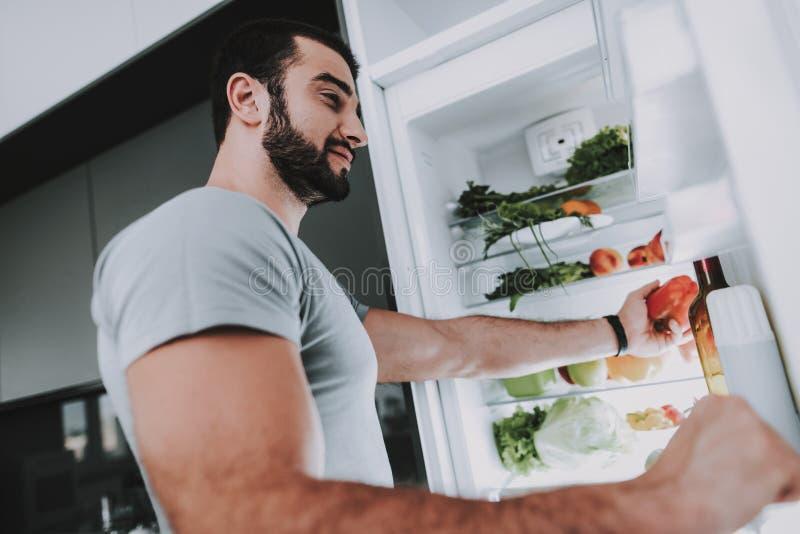En sportig man tar grönsaker från kylen royaltyfria bilder