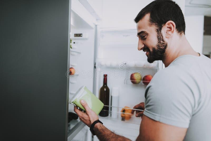 En sportig man tar grönsaker från kylen royaltyfria foton