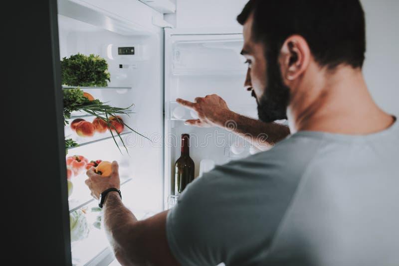 En sportig man tar grönsaker från kylen royaltyfri fotografi