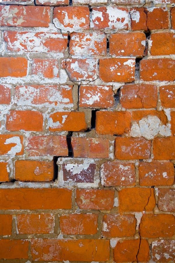 En spricka i en gammal sjaskig tegelstenvägg av ett klosterslut upp royaltyfri foto