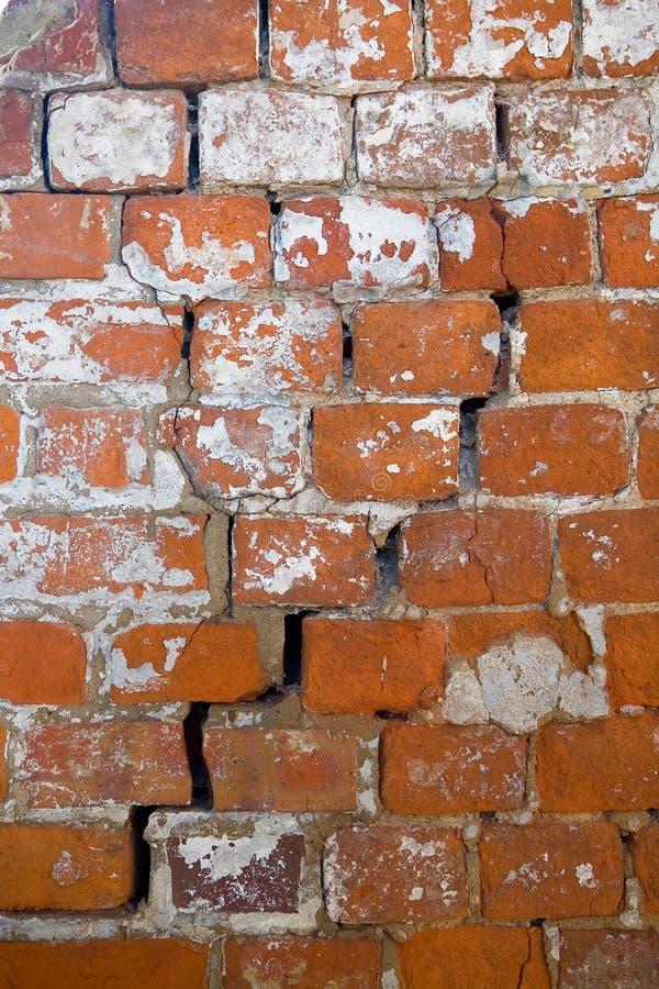 En spricka i en gammal sjaskig tegelstenvägg av ett klosterslut upp arkivfoton