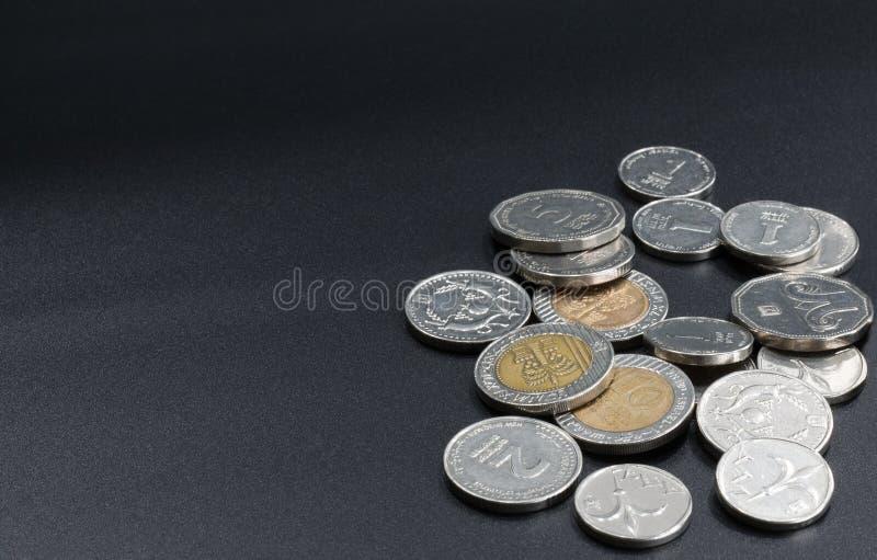 En spridning av mynt p? en svart bakgrund arkivfoto