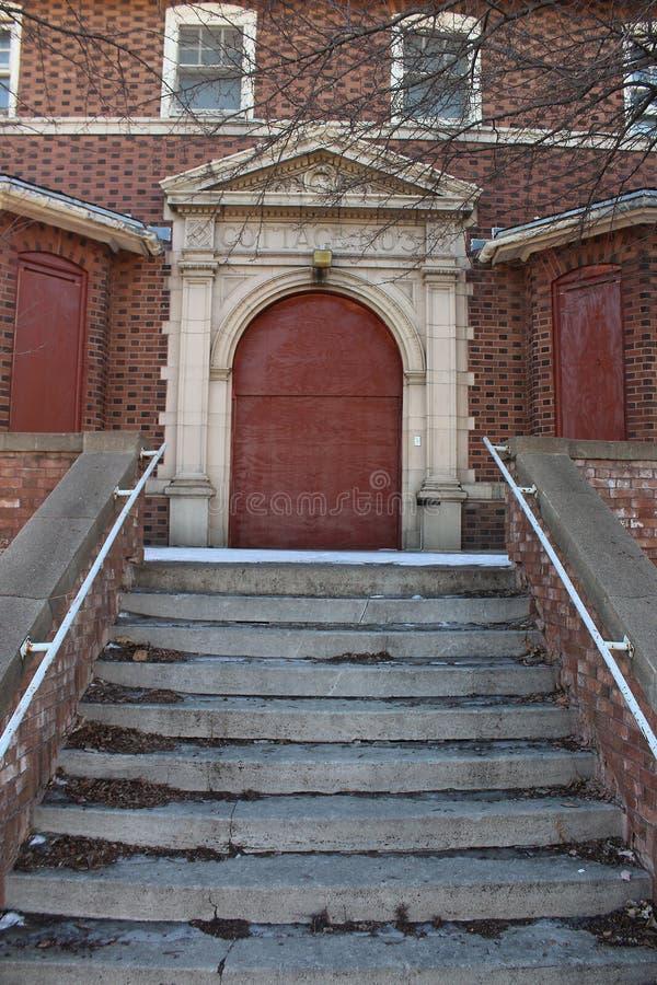 En sprucken trappa leder till en röd dörr arkivfoto