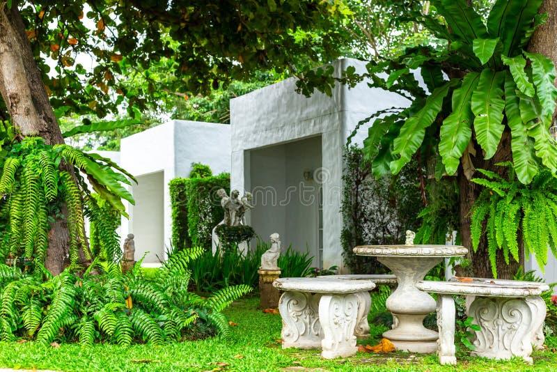 En ställde in av vita marmortabeller och stolar i blommaträdgården arkivfoton