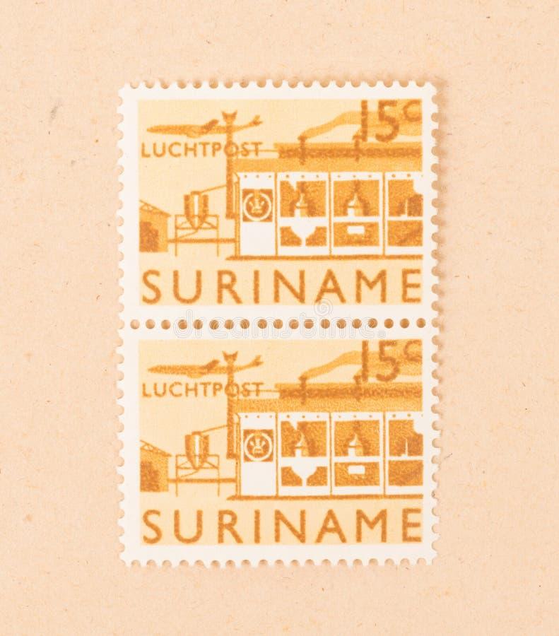 En stämpel som skrivs ut i Surinam, visar en fabrik, circa 1970 royaltyfri fotografi