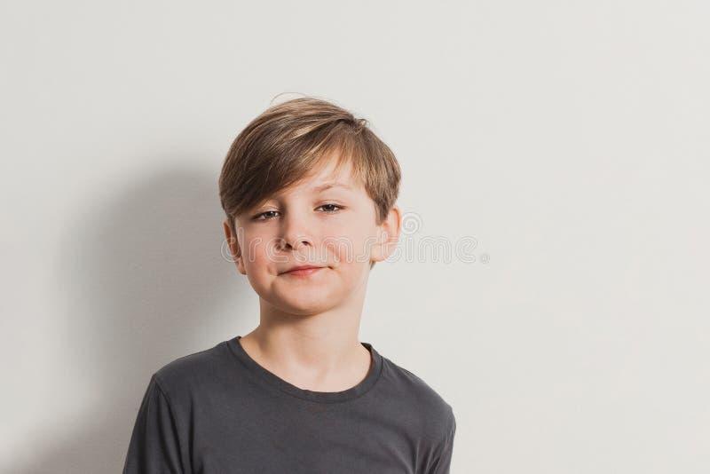 En stående av den gulliga pojken som drar framsidor, snorkig blick arkivbilder