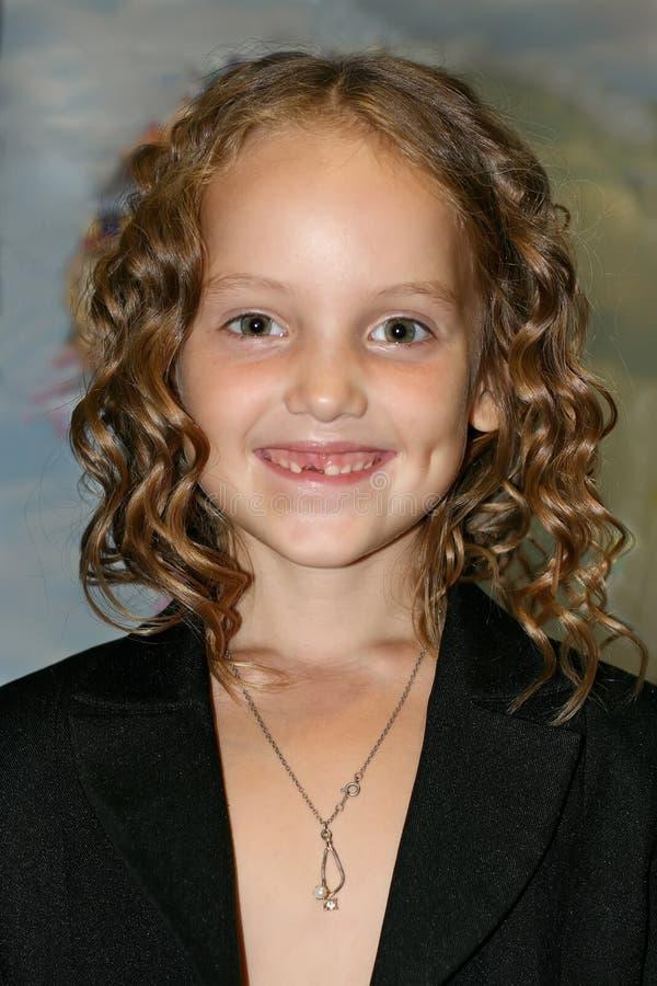En stående av den härliga le lilla flickan med krullat hår och utan foretoothen royaltyfri fotografi