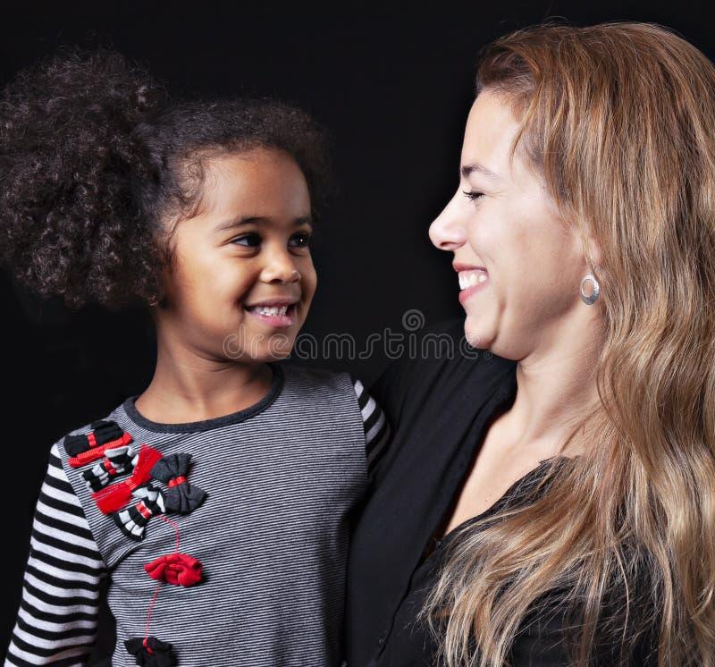 En stående av den lyckliga gladlynta afrikanska familjen som isoleras på svart bakgrund royaltyfri foto