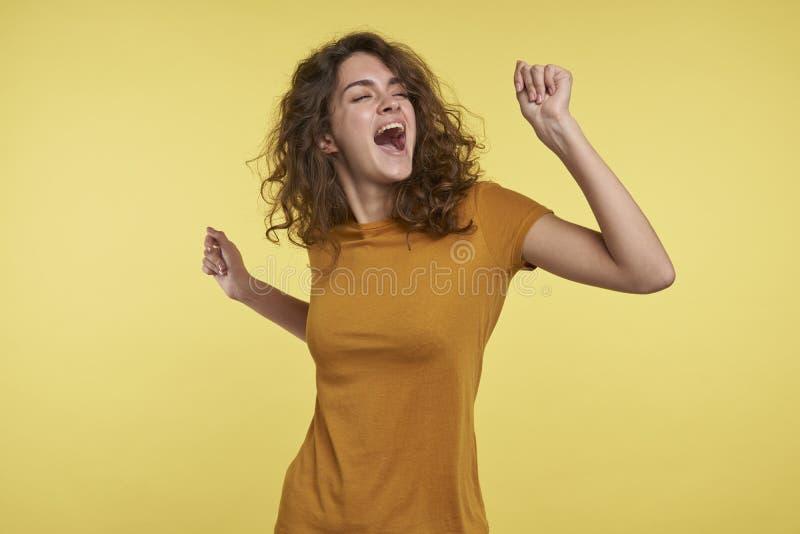 En stående av den nätta unga kvinnan med dansen och att sjunga för lockigt hår som isoleras över gul bakgrund fotografering för bildbyråer