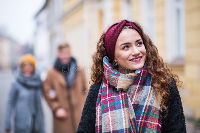 En stående av den tonårs- flickan med huvudbindeln och halsduken på gatan i vinter royaltyfria bilder