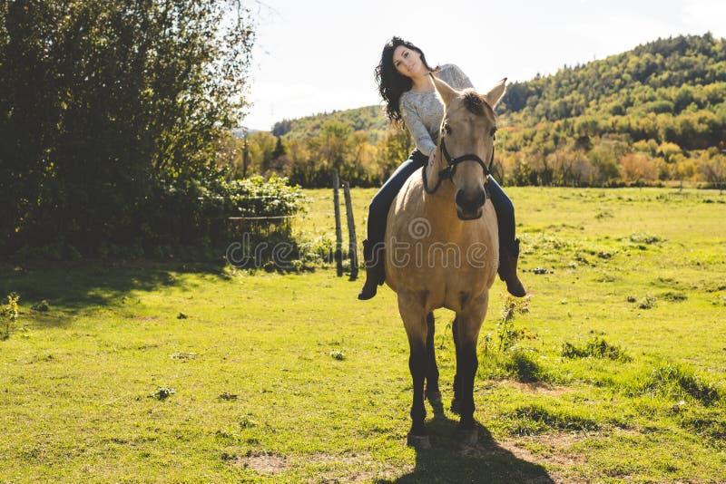 En stående av den unga härliga kvinnan med den bruna hästen utomhus royaltyfri bild