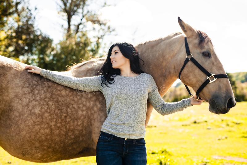 En stående av den unga härliga kvinnan med den bruna hästen utomhus arkivbild