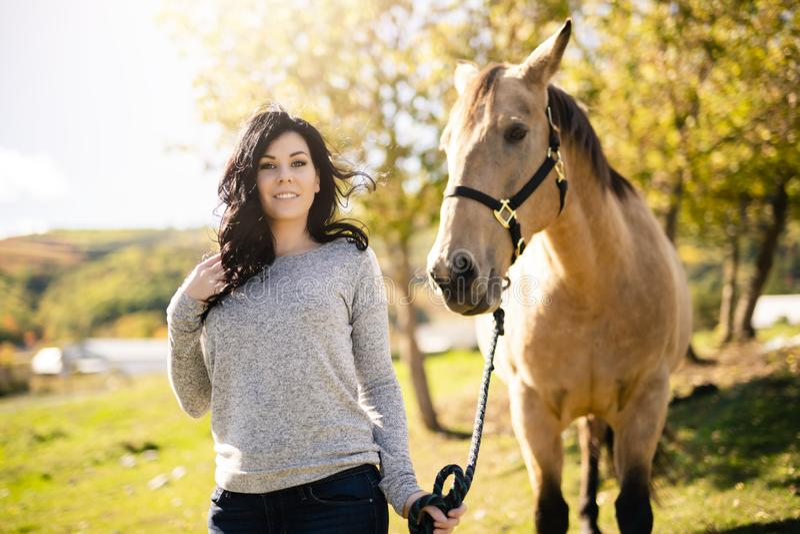 En stående av den unga härliga kvinnan med den bruna hästen utomhus arkivfoton