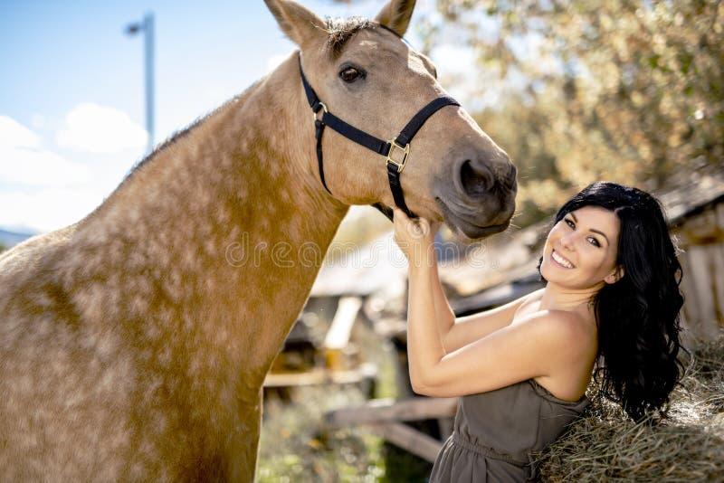 En stående av den unga härliga kvinnan med den bruna hästen utomhus royaltyfri fotografi