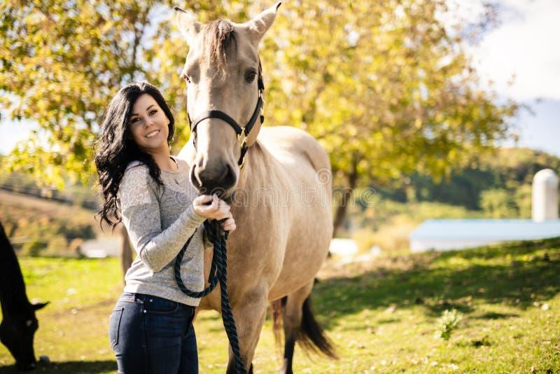 En stående av den unga härliga kvinnan med den bruna hästen utomhus royaltyfri foto