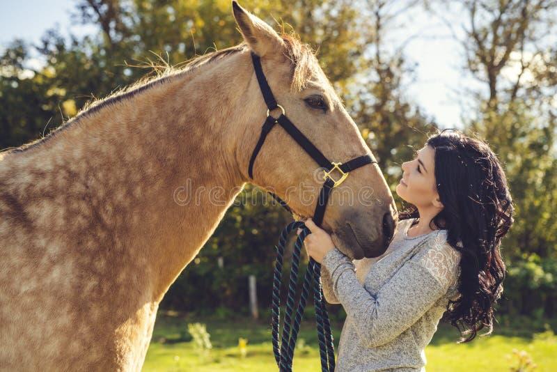 En stående av den unga härliga kvinnan med den bruna hästen utomhus royaltyfria foton