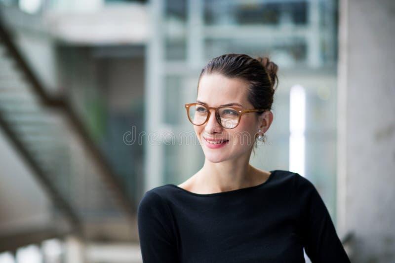 En stående av det unga affärskvinnaanseendet i korridor utanför kontor royaltyfria foton