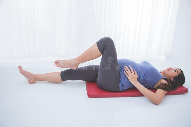 En stående av en härlig asiatisk gravid kvinna som gör på övning royaltyfria foton